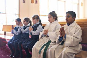 Students and alter servers in prayer at church