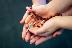 Parent a child's hand holding the Rosary
